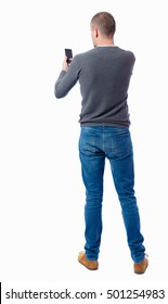 Back view of  pointing young men talking on cell phone. Young guy  gesture. Rear view people collection.  Isolated over white background. A guy in a gray sweater works on your smartphone.