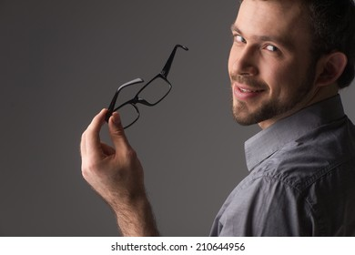 back view portrait of attractive young man holding chin. Man standing on gray background holding glasses