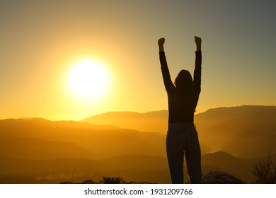 Back view portrait of a backlight silhouette of a woman celebrating vacation raising arms at sunset in the mountain