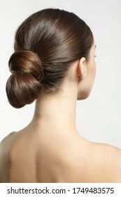 Back view portrait of beautiful young dark brunette woman. Female with creative hairdo on gray background.