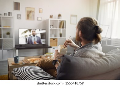 Back view portrait of contemporary man watching TV in living room, copy space