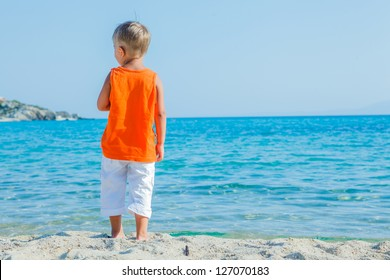 Back view portrait of cute boy at tropical beach