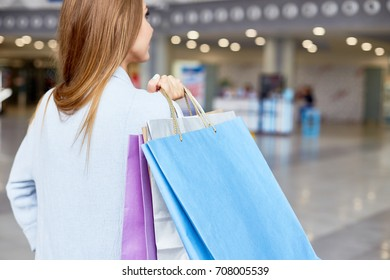 Back view portrait of elegant young woman holding paper bags shopping in mall, copy space