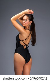 Back view portrait fashion brunette woman with long dark hair in black swimming suit, isolated on dark gray background