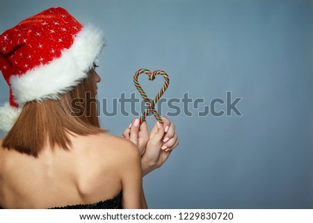 b5dbfc50c63 Back view portrait of girl in Santa hat holding Christmas candies composed  in heart shape