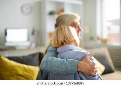 Back view portrait of happy senior couple embracing sitting on sofa at home, copy space