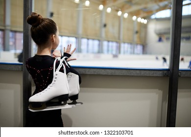 Back view portrait of little girl holding figure skates standing by ice rink and watching training, copy space