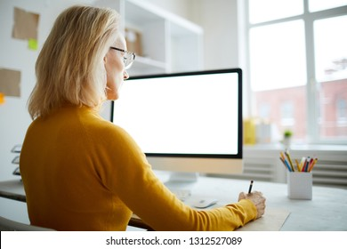 Back view portrait of mature businesswoman using computer sitting at desk in office, copy space