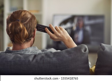 Back view portrait of modern young man watching TV at home and holding remote control, copy space