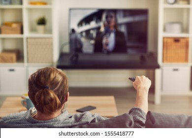 Back view portrait of modern young man watching TV at home and switching channels via remote control, copy space