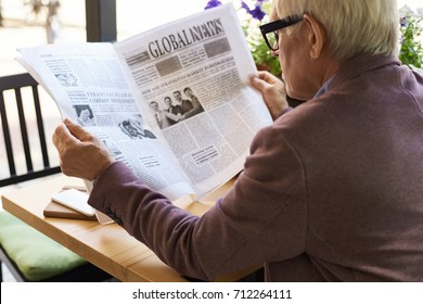 Back view portrait of senior man reading newspaper in cafe outdoors