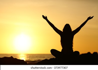 Back view portrait silhouette of a happy woman raising arms in a new day looking at warm sun at sunrise on the beach with the sea in a beautiful background