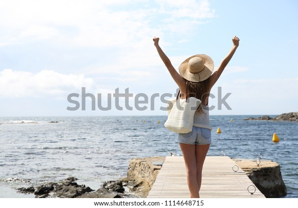 Back view portrait of a single tourist raising arms on summer on the beach