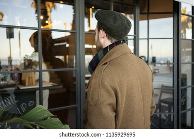 Back view portrait of stylish gentleman in front of window. Adult man wears brown british style coat and and flat cap in autumn day. Watches his own reflection on glass next to restaurant.