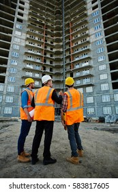 Back view portrait of three workmen wearing reflective orange vests and hard hats standing on construction site against unfinished apartment building, discussing it