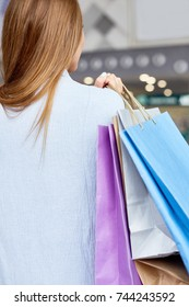 Back view portrait of unrecognizable young woman holding paper bags shopping in mall