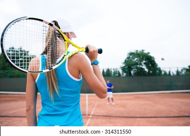 Back view portrait of a woman playing in tennis outdoors