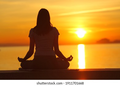 Back view portrait of a woman silhouette doing yoga exercises at sunset on the beach