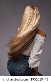 Back view portrait of a woman sitting on the chair, long hair.