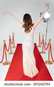 Back view portrait of a woman walking on red carpet