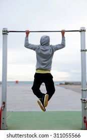 Back view portrait of  young bodybuilder in active wear doing pull ups on the horizontal bar outdoors, strong athlete doing exercise in a cloudy morning outside, fit man working out at street gym