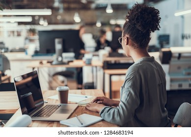 Back view portrait of young lady looking at colleagues while sitting at wooden table with laptop, cup of coffee and stationery