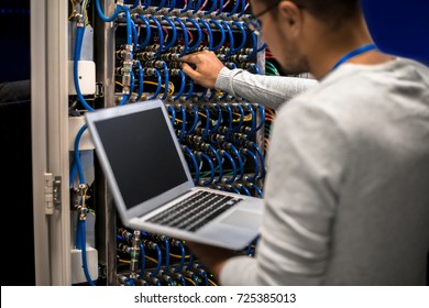 Back view portrait of young man working with supercomputer connecting blade server cables and  checking data on laptop