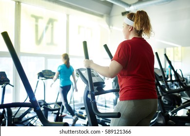 Back view  portrait of young obese woman working out in gym: using ellipse  machine with effort to lose weight