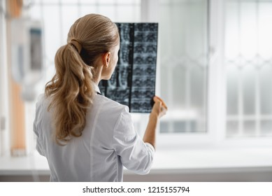 Back view portrait of young woman in white lab coat analyzing radiography results. Focus on lady