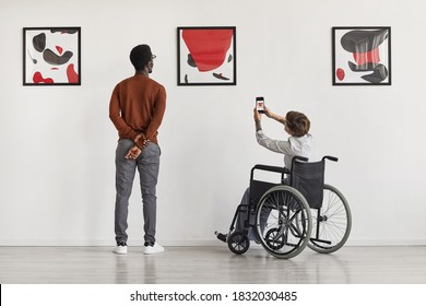 Back view portrait of young woman using wheelchair taking photo of artwork while visiting accessible museum, copy space
