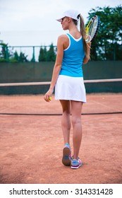 Back view portrait of a young woman playing in tennis outdoors