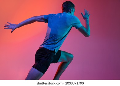 Back view. Portrat of Caucasian male athlete, runner training isolated on pink studio background with blue neon filter, light. Concept of action, motion, speed, healthy lifestyle. Copyspace for ad. - Shutterstock ID 2038891790