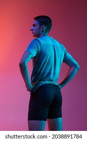 Back view. Portrat of Caucasian young sportive man in sportswear standing isolated on pink background with blue neon filter, light. Concept of action, motion, speed, healthy lifestyle. - Shutterstock ID 2038891784