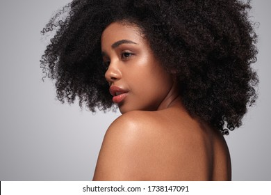 Back view of pretty ethnic woman with clean skin and curly hair looking away over shoulder after spa procedure against gray background