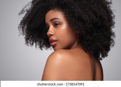 Vue arrière d'une jolie femme ethnique à la peau propre et aux cheveux bouclés regardant au-dessus de l'épaule après la procédure de spa sur fond gris