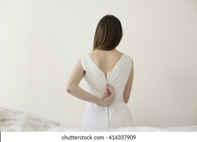 Back view of pretty woman, unzipping her tight white dress sitting on the bed