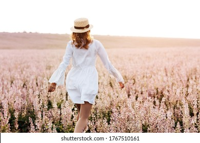 Back view of a pretty young woman in white dress holding straw hat running walking at the sage flower field. Beautiful girl enjoying a field of flowers, relaxing outdoors, having fun, harmony concept.