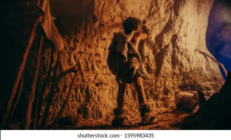 Back View of Primitive Prehistoric Neanderthal Wearing Animal Skin Draws Animals and Abstracts on the Walls at Night. Creating First Cave Art with Petroglyphs, Rock Paintings Illuminated by Fire