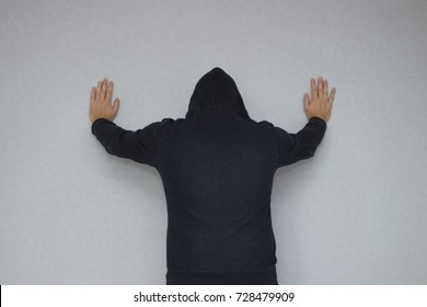 Back view of prisoner in a hoody with hands up get arrested against grey background.