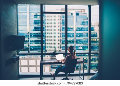 Back view of professional designer working at home on new project via high speed internet connection on digital netbook with blank screen area sitting near window with cityscape i own modern apartment