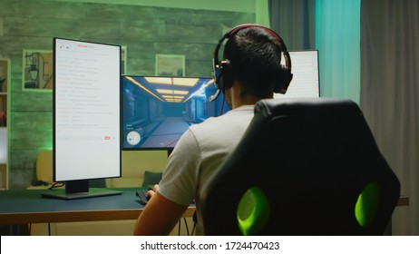 Back view of professional gamer streaming his competition on triple monitor setup with two streaming chats open