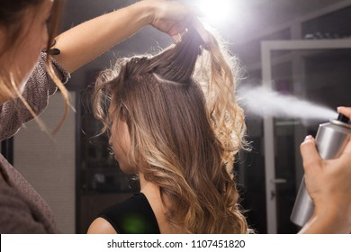 Back view of professional hairdresser fixing a coiffure with curls of a young client using a hair spray in a beauty salon