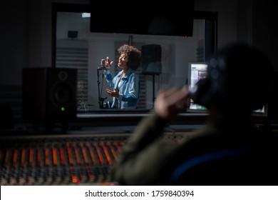 Zurück-Ansicht des professionellen männlichen Tonproduzenten mit Kopfhörern nimmt ein neues Lied mit einer jungen afrikanischen Sängerin in einem Musikstudio auf.