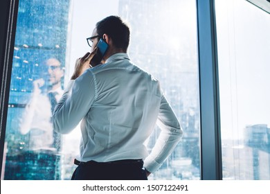 Back view of proud CEO dressed in official wear calling via mobile phone standing in office interior, male entrepreneur talking with client via cellphone during work day in enterprise corporation