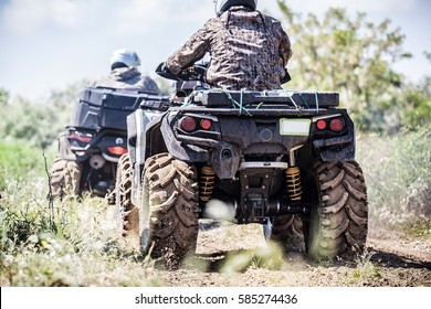Back view of quad bike  zipping along a country road.