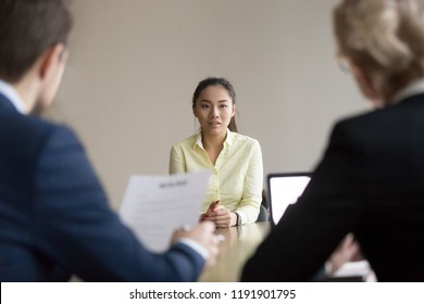 Back view of recruiters interview young Asian job candidate asking questions, reading her resume, hr managers hiring employee, considering cv experience, worried intern talk at recruitment process