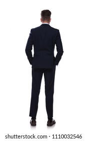 back view of relaxed businessman in navy suit standing on white background with hands in pockets