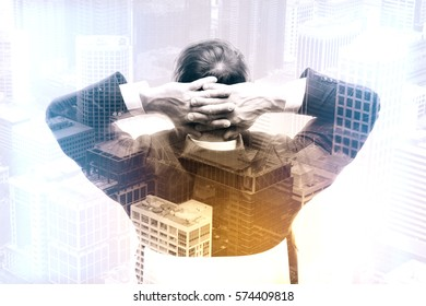 Back view of relaxing businessman on city background. Success concept. Double exposure