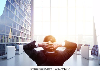 Back view of relaxing young businessman on abstract meeting room interior background with sunlight and copy space. Success and executive concept. Double exposure