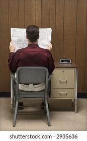 Back view of retro businessman sitting at desk reading paper.